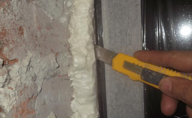 Удаление излишков монтажной пены, которая легко удаляется при помощи обычного канцелярского ножа.